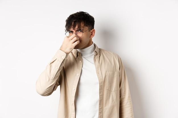 Immagine di un ragazzo disgustato che si chiude il naso per un odore terribile, guardando qualcosa di disgustoso e puzzolente, in piedi su sfondo bianco