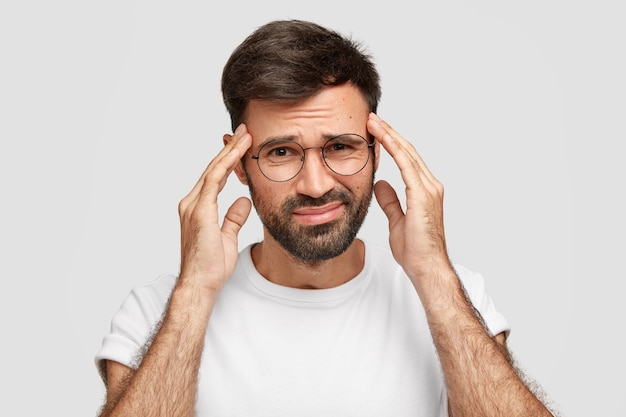 Image of displeased bearded male suffers from strong headache after working all night, has fatigue expression, keeps hands on temples, frowns face, poses against white wall. bad feeling