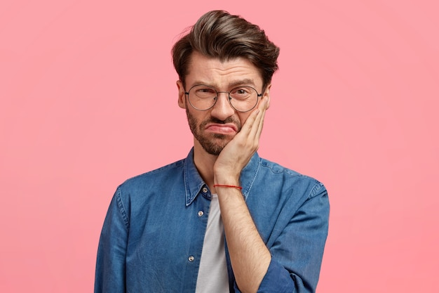 Image of displeased bearded young guy has sullen facial expression, touches cheek with hand, dressed in fashionable denim shirt, poses against pink wall, being dissatisfied with something