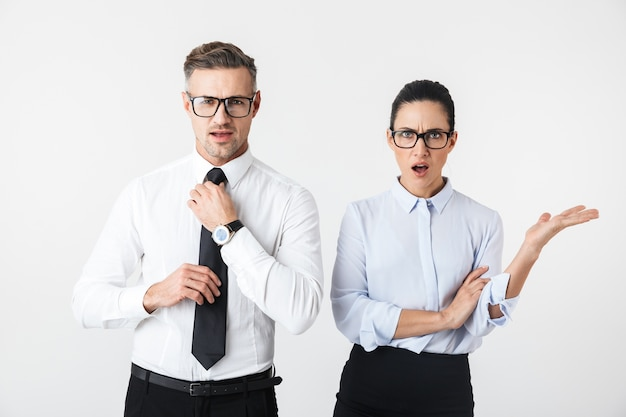 Image of displeased business colleagues couple isolated over white wall.