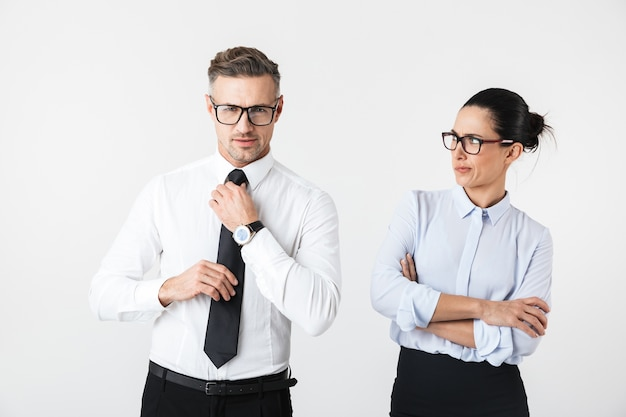 Image of displeased business woman looking at her colleague man isolated over white wall.