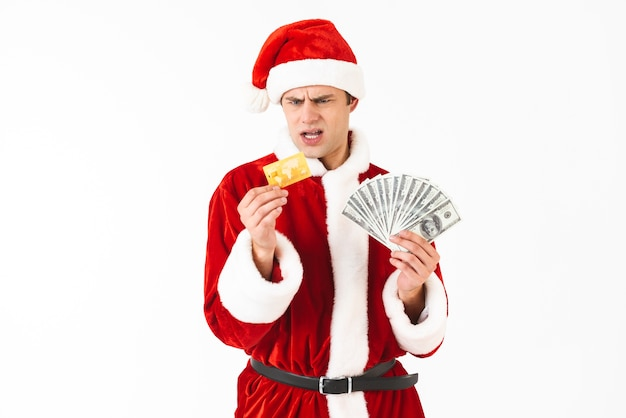 Image of displeased man 30s in santa claus costume holding dollar bills and credit card