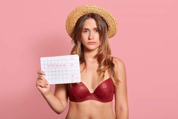 Image of displeased young european female suffering from pain in stomach, holding period calendar, has unhappy look, feels unwell, has menstruation, posing on studio wall. painful periods concept