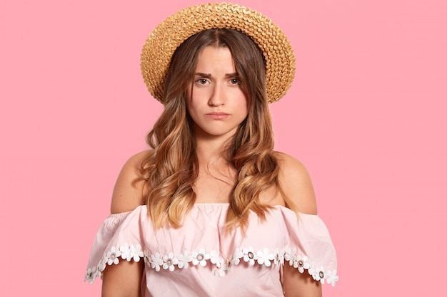Image of displeased young woman with sad expression, doesnt like something, wears headgeear and fashionable blouse, isolated over pink wall. human negative emotions and feelings concept