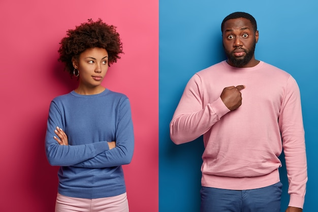 Image of dissatisfied afro american woman feels offended after dispute with husband, keeps hands crossed and looks angrily at him