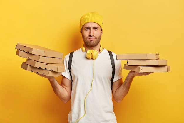 Image of dissatisfied caucasian man has sullen face expression, holds cardboard pizza boxes, feels tired after delivering food all day long, wears casual outfit, isolated on yellow  wall