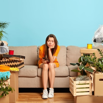 Image of dissatisfied european woman sits alone at sofa in living room, feels lonely and frustrated, holds modern cellular, surrounded with cardboard boxes after relocation, has much work to do