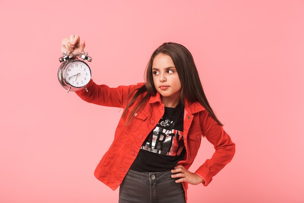 Image of dissatisfied girl 8-9y in casual holding alarm clock while standing, isolated over red wall