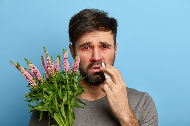 Image of dissatisfied ill bearded man has red eyes, sprays nose with drops to cure sneezing and allergic symptoms, has reaction on trigger, swollen red eyes, poses indoor. allergy sickness concept