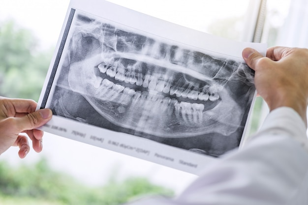 Image of doctor or dentist holding and looking at x-ray