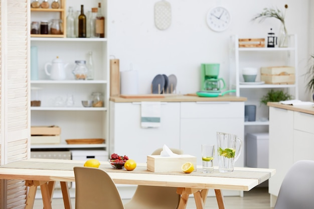 Image of domestic kitchen with white furniture and table with drinks and fruits on it in the house