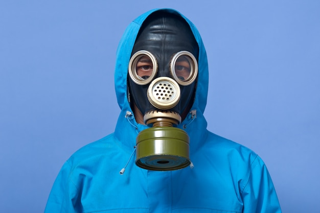 Image of ecologist wearing gas mask frights with pouring dangerous chemicals to ground