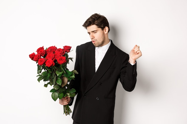 Image of elegant and sassy man in black suit, looking confident and holding bouquet of red roses, going on a romantic date, standing against white background.