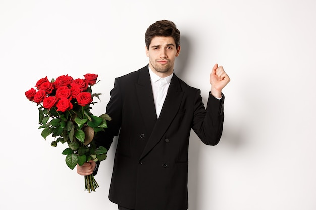 Image of elegant and sassy man in black suit, looking confident and holding bouquet of red roses, going on a romantic date, standing against white background