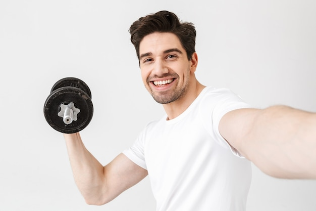 Image of emotional happy excited young man posing isolated over white wall holding dumbbell make exercise take a selfie by camera.