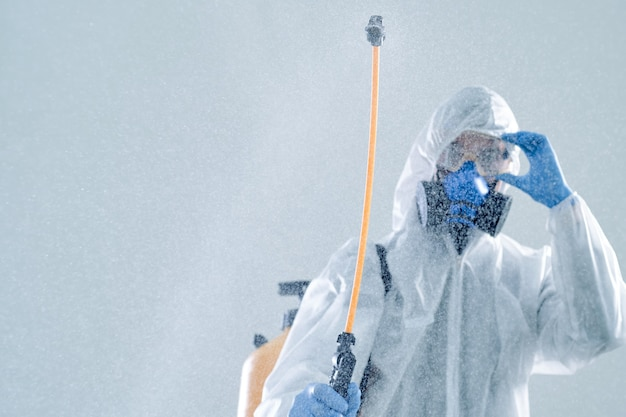 Image of an employee of the sanitary service with a can of disinfectant