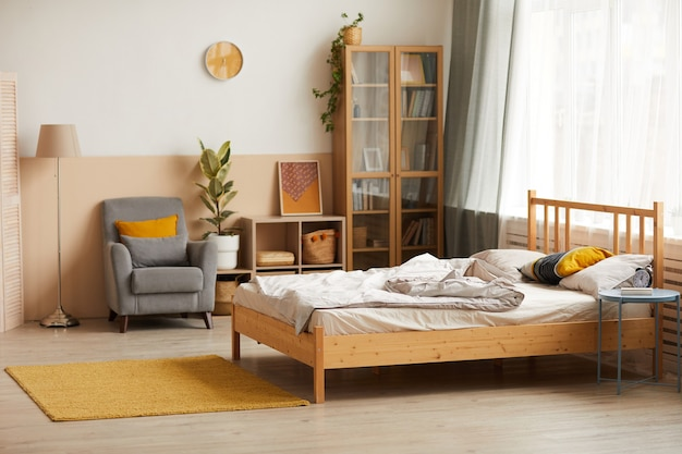 Image of empty modern bedroom with bed bookcase and armchair