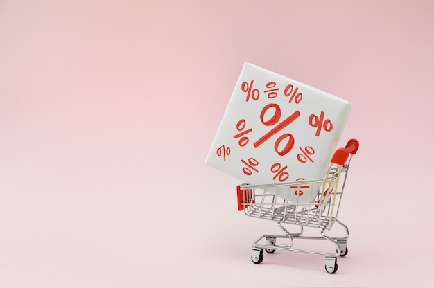 Image of empty shopping trolley or cart with box of discount percent sale black friday products