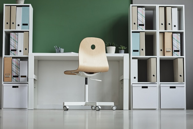 Image of empty workplace with chair and bookcase at office