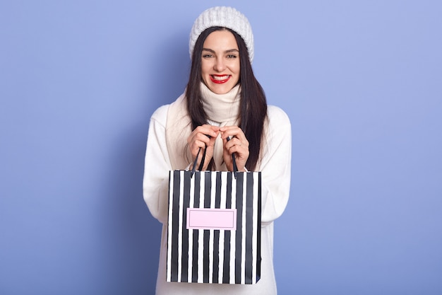 Image of energetic positive lady with black hair and red lips, holding present in paper striped bag, smiling sincerely
