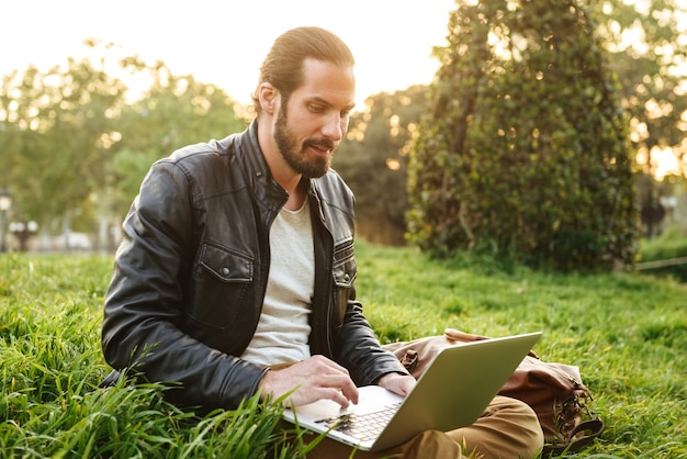 Image of european bearded man in white t-shirt sitting on grass in green park, and working on silver notebook
