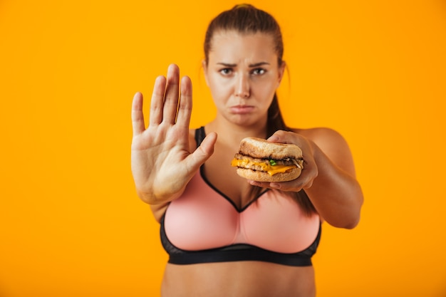 Image of european chubby woman in tracksuit doing stop gesture while holding sandwich, isolated over yellow background