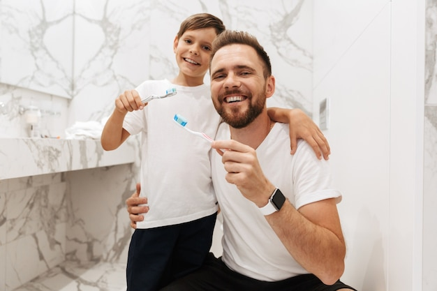Image of european father and son smiling, and cleaning teeth together in bathroom