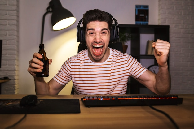 Image of european guy 20s wearing headphones drinking beer, while sitting at desk with computer in room and looking at camera