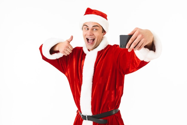 Image of european man 30s in santa claus costume holding cell phone and taking selfie