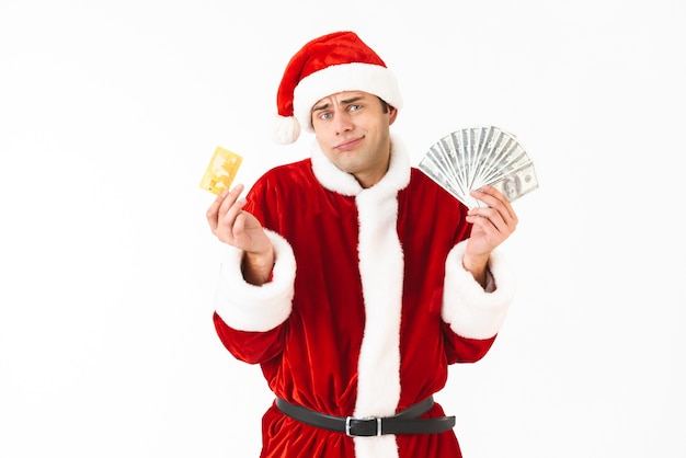 Image of european man 30s in santa claus costume holding dollar bills and credit card