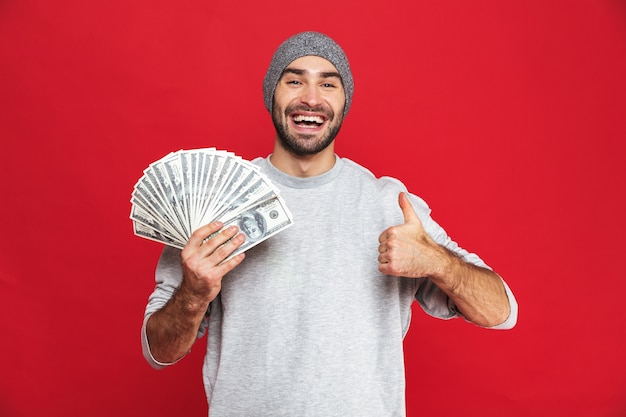 Image of european man 30s wearing hat holding money fan, isolated