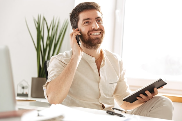 Image of european office worker 30s wearing white shirt using smartphone and notebook, while sitting at table in modern workplace