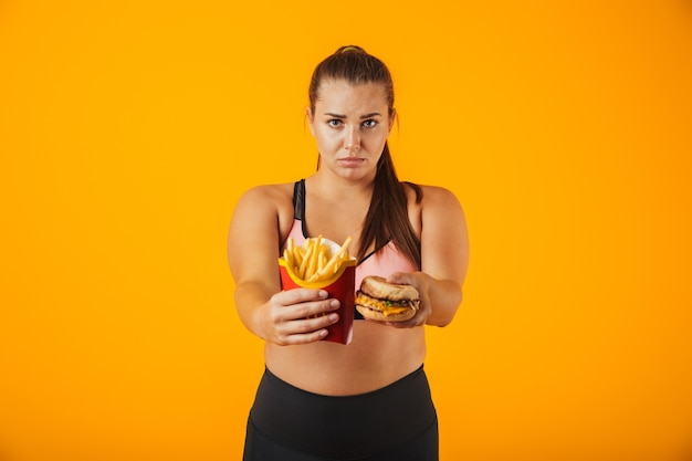 Image of european overweight woman in tracksuit doing stop gesture while holding sandwich and french fries, isolated over yellow background