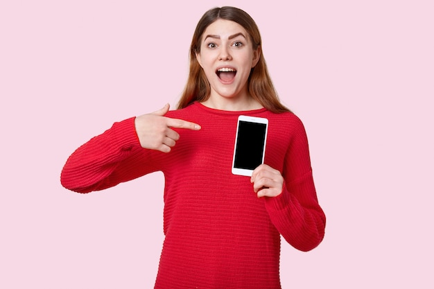 Image of european positive young woman points at cell phone with empty screen, dressed in red sweater, advertises new gadget