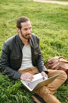 Image of european stylish guy in leather jacket sitting on grass in green park, and using silver notebook