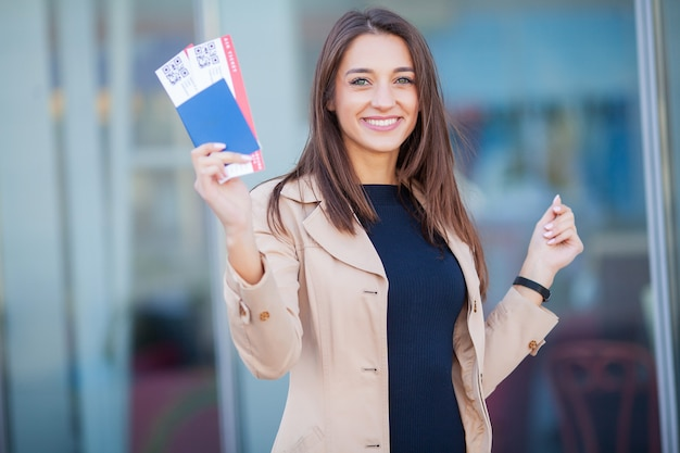 Image of european woman having beautiful brown hair smiling while holding passport and air tickets