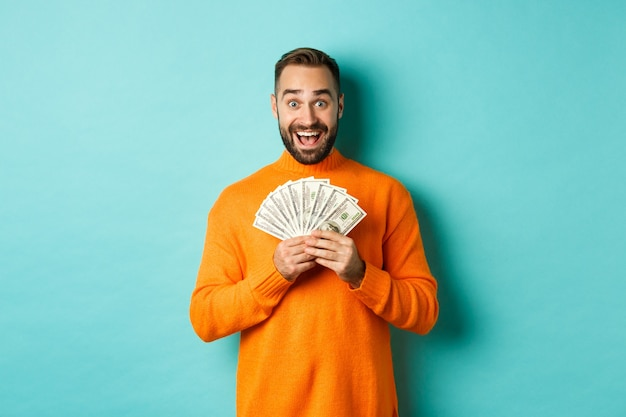 Image of excited bearded guy holding money and rejoicing, winning cash prize, standing against light blue background