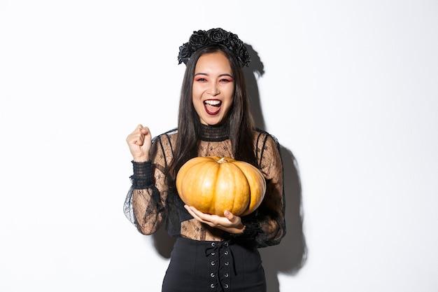 Immagine di bella donna asiatica eccitata che celebra halloween, indossando abiti da strega e tenendo la zucca, urlando di gioia.