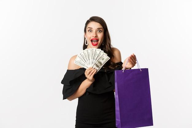 Immagine di eccitata bella donna in abito nero, andare a fare shopping, tenendo la borsa e dollari, in piedi su sfondo bianco.