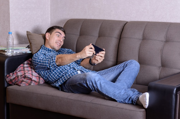 Image excited of a bristle man dressed in shirt in a cage print, jeans and white socks, lies on sofa in home and playing at smatphone. passionate about the game