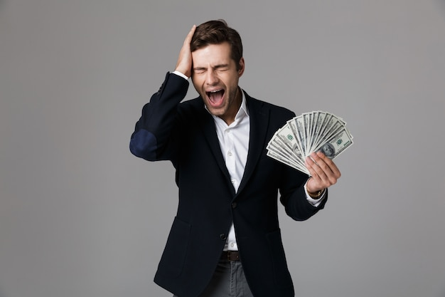 Image of excited businessman 30s in suit smiling and holding fan of money in dollar banknotes, isolated over gray wall