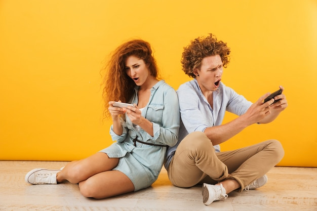 Image of excited couple or friends man and woman sitting on floor back to back and playing games on smartphones, isolated over yellow background