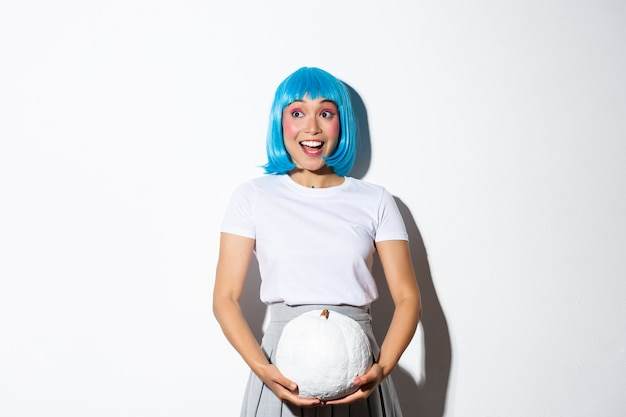 Image of excited cute asian girl looking at upper left corner banner about halloween, holding white pumpkin, wearing blue wig for party.