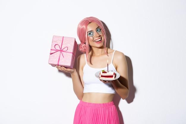 Immagine della ragazza carina eccitata con parrucca rosa, scatola tremante con regalo e vagare cosa c'è dentro, tenendo un pezzo di torta di compleanno, celebrando il b-day.