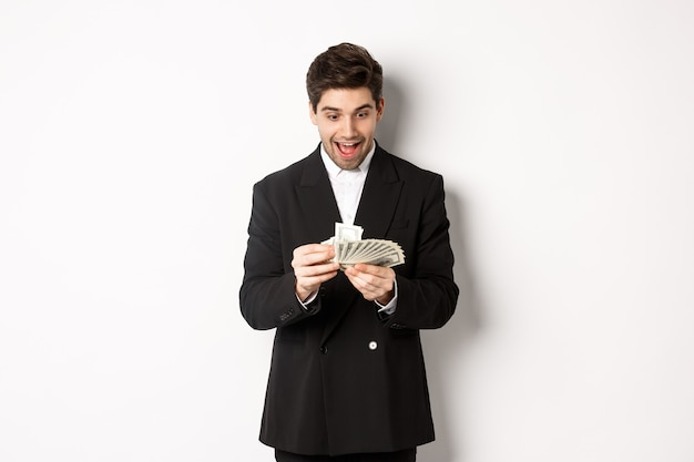 Image of excited handsome businessman, counting money and smiling amused, standing against white background in suit.