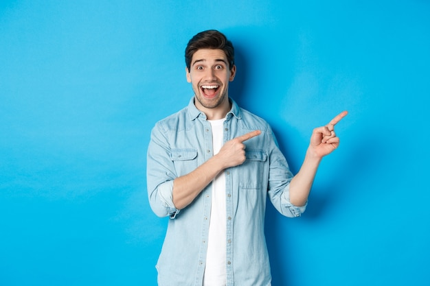 Image of excited handsome man in casual outfit, showing advertisement, pointing fingers right at copy space and smiling, standing against blue background