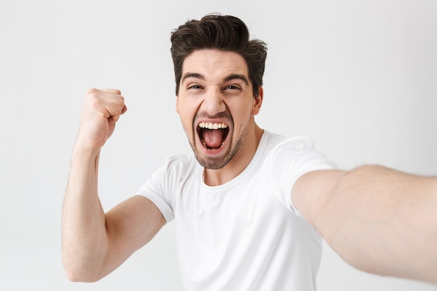 Image of excited happy young man posing isolated over white wall  make a selfie by camera make winner gesture.