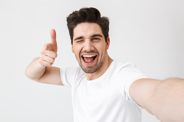 Image of excited happy young man posing isolated over white wall  make a selfie by camera pointing to you.
