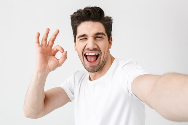 Image of excited happy young man posing isolated over white wall  make a selfie by camera showing okay gesture.