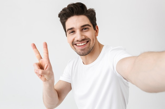 Image of excited happy young man posing isolated over white wall  make a selfie by camera showing peace gesture.